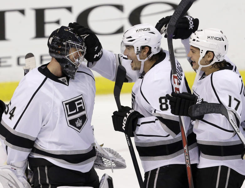 Los Angeles Kings defenseman Drew Doughty, second from left, and left wing Daniel Carcillo (17) celebrate with goalie Ben Scrivens after the Kings defeated the Florida Panthers 3-0 during an NHL hockey game, Sunday, Oct. 13, 2013, in Sunrise, Fla. (AP Photo/Wilfredo Lee)