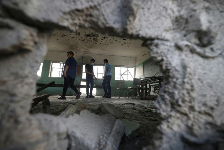 Palestinian students inspect a classroom at a school destroyed during the recent 11-day war between Israel and the Palestinian Hamas movement, on the first day of the new academic year in Gaza City, on August 16, 2021