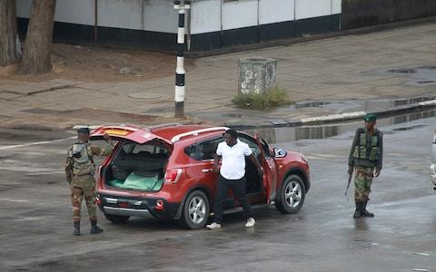 Armed soldiers search a vehicle on the road leading to President Robert Mugabe's office in Harare - Credit: AP