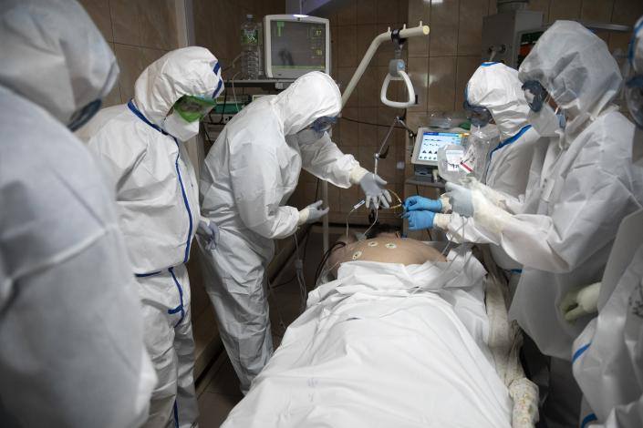 In this photo taken on Friday, May 15, 2020, Dr. Osman Osmanov, center, and his colleagues treat a coronavirus patient on artificial lung respiration at an intensive care unit of the Filatov City Clinical Hospital in Moscow, Russia. Moscow accounts for about half of all of Russia's coronavirus cases, a deluge that strains the city's hospitals and has forced Osmanov to to work every day for the past two months, sometimes for 24 hours in a row. (AP Photo/Pavel Golovkin)