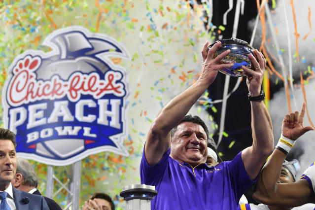 LSU coach Ed Orgeron holds the trophy after the team's Peach Bowl NCAA semifinal college football playoff game against Oklahoma, Saturday, Dec. 28, 2019, in Atlanta. LSU won 63-28. (AP Photo/John Amis)