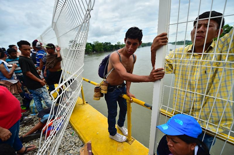 Honduran migrants heading in a caravan to the US prepare to jump into the Suchiate River from the Guatemala-Mexico international border bridge in Ciudad Hidalgo, Mexico, on October 20, 2018 (AFP Photo/Pedro Pardo                    )