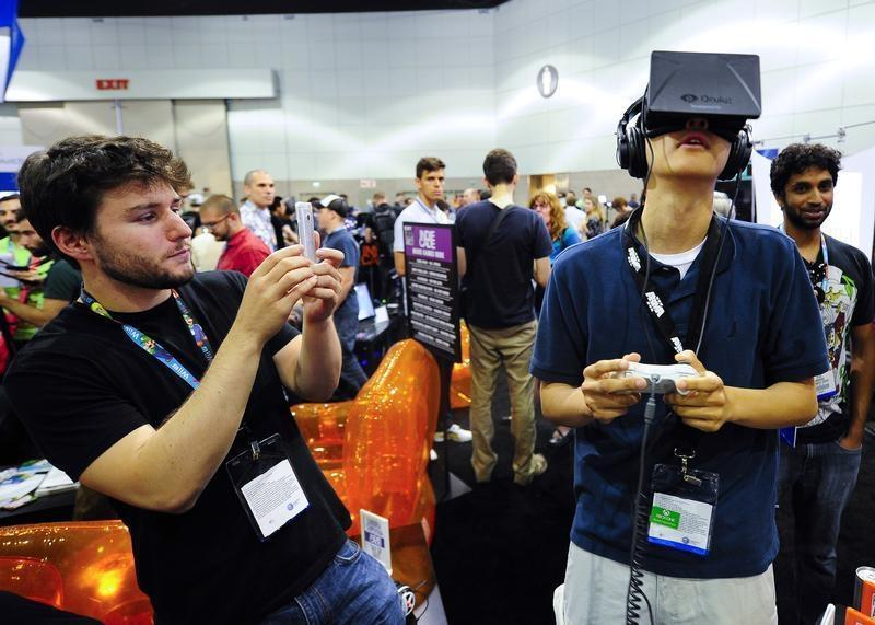 """Software designer Julian Kantor who created """"The Recital"""" takes a picture of Jonathan Feng as he uses the Oculus Rift virtual reality headset to experience his program during E3 in Los Angeles"""