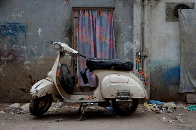 <p>A Vespa scooter stands near a workshop, where old Vespa parts are painted, on a street in Karachi, Pakistan, Feb. 28, 2018. (Photo: Akhtar Soomro/Reuters) </p>