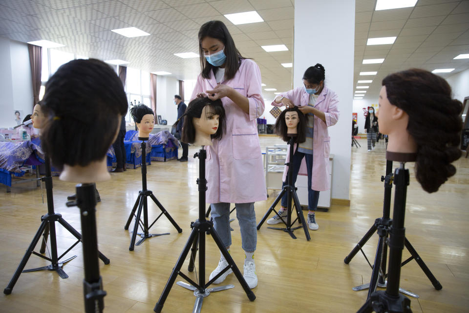 Students braid wigs during a class at the Peyzawat Training School in Peyzawat County in China's far west Xinjiang region, as seen during a state-organized tour for foreign media on April 19, 2021. Four years after Beijing's brutal crackdown on largely Muslim minorities native to Xinjiang, Chinese authorities are dialing back the region's high-tech police state and stepping up tourism. But even as a sense of normality returns, fear remains, hidden but pervasive. (AP Photo/Mark Schiefelbein)