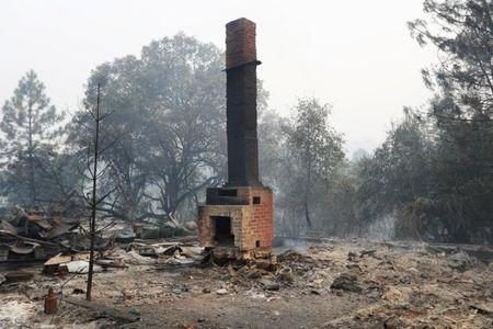 A chimney stands amidst remains of a home destroyed by the Detwiler fire in Mariposa