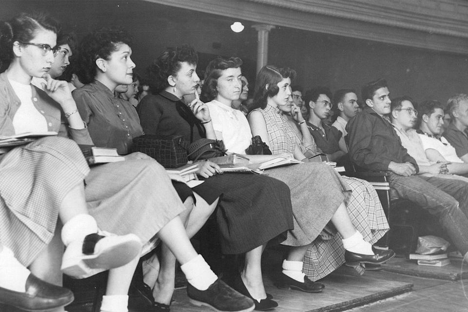 <p>High school students sit attentively during an assembly. </p>