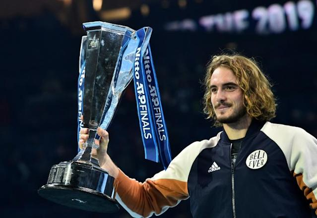 Stefanos Tsitsipas poses with the ATP Finals trophy (AFP Photo/Glyn KIRK )