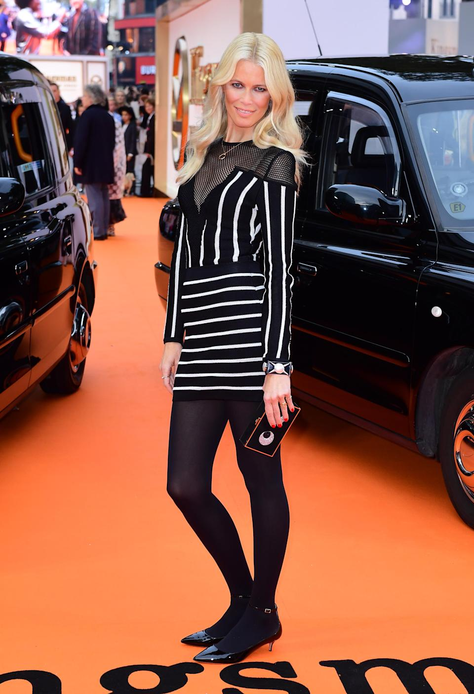 <p>The supermodel went for a slightly more casual look wearing a striped monochrome mini dress by Balmain and black kitten heels.<br><i>[Photo: PA]</i> </p>