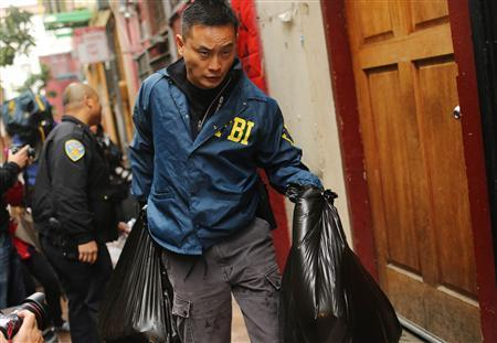 An investigator with the U.S. Federal Bureau of Investigation (FBI) removes bags from the Ghee Kung Tong building, which houses the Chinese Freemasons, in the Chinatown neighborhood in San Francisco, California March 26, 2014. REUTERS/Robert Galbraith