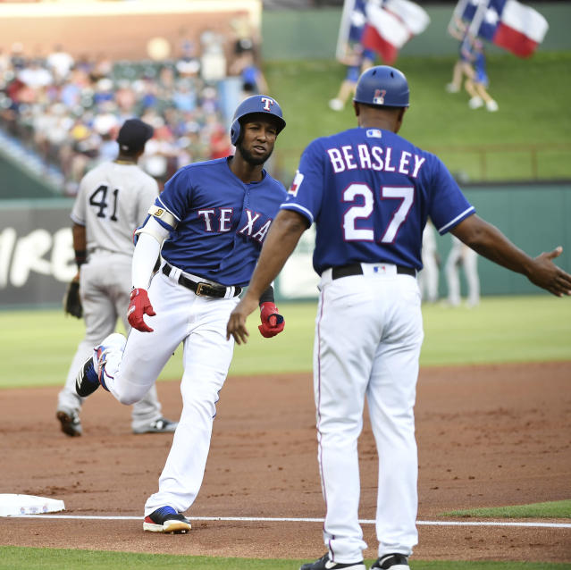 Texas Rangers' Jurickson Profar is congratulated by third base coach Tony Beasley (27) as he rounds third base on a three-run home run in the first inning of the team's baseball game against the New York Yankees, Tuesday, May 22, 2018, in Arlington, Texas. (AP Photo/Jeffrey McWhorter)