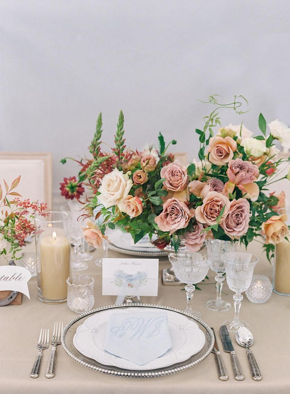 <p>Table details included pewter rimmed chargers paired with white china with scalloped edges, Tuscan flatware, and etched glassware. Footed silver urns and julep cups held centerpieces with roses in various neutral tones. Beige pillar candles placed in glass holders and small tea candles in etched glass votives were the finishing touches.</p>