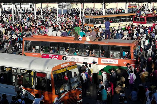 Migrant workers and their family members gather outside the Anand Vihar bus terminal to leave for their villages during a government-imposed nationwide lockdown as a preventive measure against the COVID-19 coronavirus in New Delhi on March 28, 2020. - Tens of thousands of migrant workers and their famiies on March 28 fought and shoved their way onto buses organised by India's most populous state to get them to their home towns amid the coronavirus pandemic. (Photo by Bhuvan BAGGA / AFP) (Photo by BHUVAN BAGGA/AFP via Getty Images)