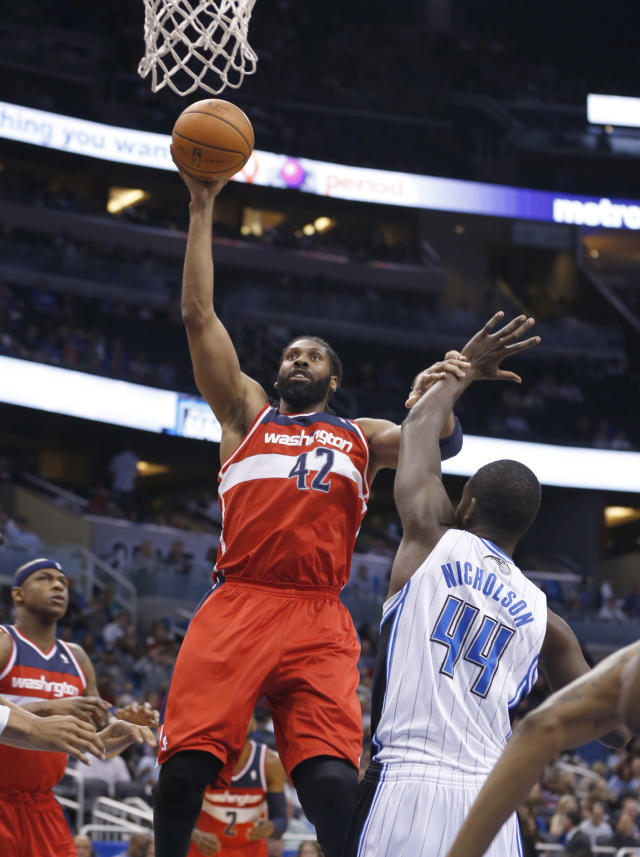 Washington Wizards forward Nene Hilario (42), of Brazil, shoots over Orlando Magic forward Andrew Nicholson (44), of Canada, during the first half of an NBA basketball game in Orlando, Fla., Friday, April 11, 2014. (AP Photo/Reinhold Matay)