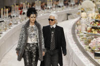 """FILE - In this Tuesday, Dec. 6, 2011 file photo, German fashion designer Karl Lagerfeld with British model Stella Tennant, left, acknowledges applause at the end of the presentation of his Paris-Bombay collection for Chanel, presented at the Grand Palais in Paris. Tennant, the aristocratic British model who was a muse to designers including Karl Lagerfeld and Gianni Versace, has died suddenly at the age of 50, her family said Wednesday, Dec. 23, 2020. The family asked for their privacy to be respected and said Tennant was """"a wonderful woman and an inspiration to us all."""" Police Scotland said there were no suspicious circumstances. (AP Photo/Remy de la Mauviniere, File)"""