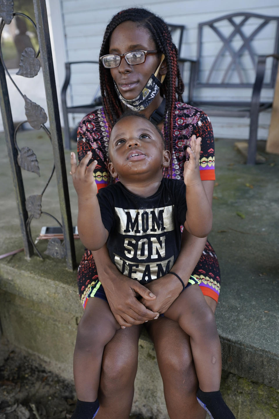 Fakisha Fenderson and her son Tyler sit on the porch of her parent's home in Laurel, Miss., Monday, Aug. 31, 2020. Fenderson's weekly unemployment allotment is under $100, effectively eliminating her chance at receiving the $300 weekly supplement proposed by President Trump's executive order. (AP Photo/Rogelio V. Solis)