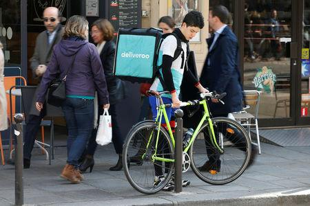 A cyclist prepares to mount a bicycle as he delivers a food order for Deliveroo, an example of the emergence of what is known as the 'gig economy', in Paris
