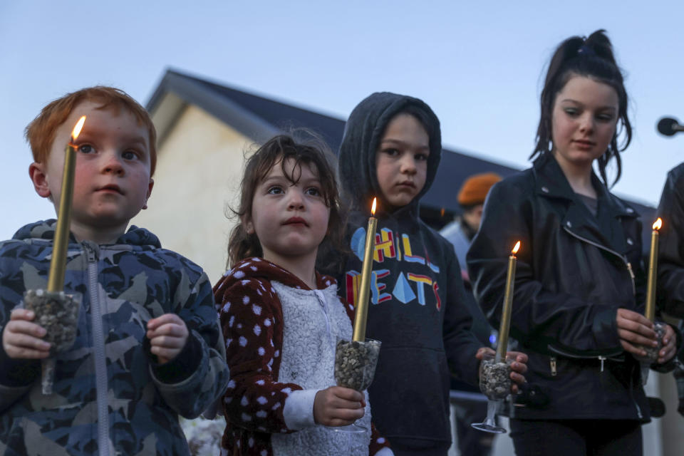 Children hold a candle light vigil outside the home in Timaru, New Zealand, Thursday, Sept. 23, 2021 for sisters Maya, Karla and Liane Dickason, originally from South Africa, who were killed in their home on Sept. 16. People in the town of Timaru held an evening vigil outside the home of three young girls who were killed last week in a crime that shocked New Zealand. The girls' mother Lauren Dickason has been charged with murder. (George Heard/New Zealand Herald via AP)