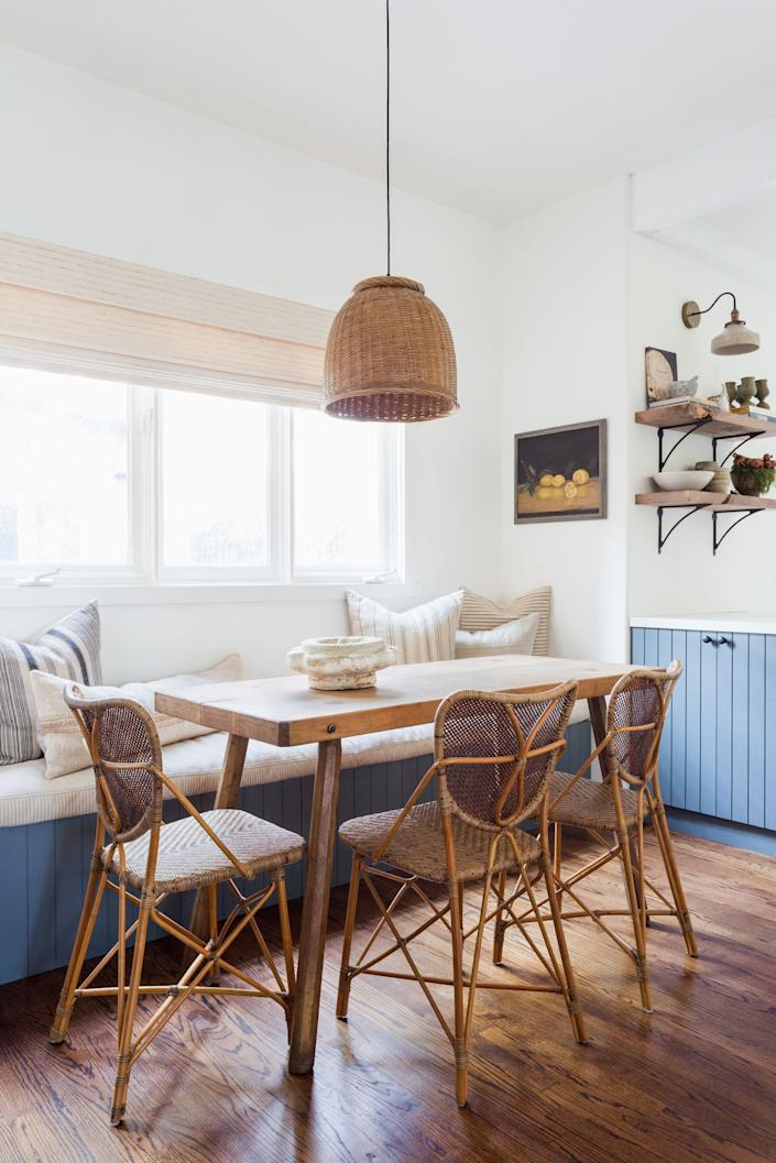 "<div class=""caption""> The breakfast nook is the relaxed space where the family of five can gather for informal meals. The table is an antique French butcher block sourced from <a href=""https://www.dekorliving.com/"" rel=""nofollow noopener"" target=""_blank"" data-ylk=""slk:Dekor"" class=""link rapid-noclick-resp"">Dekor</a> and paired with chairs from <a href=""https://www.palecek.com/"" rel=""nofollow noopener"" target=""_blank"" data-ylk=""slk:Palecek"" class=""link rapid-noclick-resp"">Palecek</a>. The pendant is a vintage rattan shade sourced by Boesch at the Rose Bowl Flea Market and the painting of lemons is another vintage piece that she found. </div>"