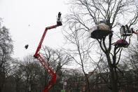 Two cherry pickers approach an HS2 Rebellion treetop camp, as a protester, left, uses a zip line between two trees, in an encampment in Euston Square Gardens in central London, Wednesday Jan. 27, 2021. Protesters against a high-speed rail link between London and the north of England said Wednesday that some of them have been evicted from a park in the capital after they dug tunnels and set up a makeshift camp. (Aaron Chown/PA via AP)