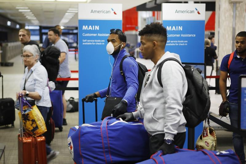 FILE - In this March 15, 2020, file photo, Toronto Blue Jays minor league baseball player Jesus Navarro, left center, wears a mask while he prepares to fly home along with his teammates from the Dominican Republic at Tampa International Airport in Tampa, Fla. Unlike the NFL, NBA or Major League Baseball that can run on television revenue, it's impossible for some minor sports leagues in North America to go on in empty stadiums and arenas in light of the coronavirus pandemic. These attendance-driven leagues might not play again at all in 2020, putting some teams in danger of surviving at all and potentially changing the landscape of minor league sports in the future. (Octavio Jones/Tampa Bay Times via AP, File)