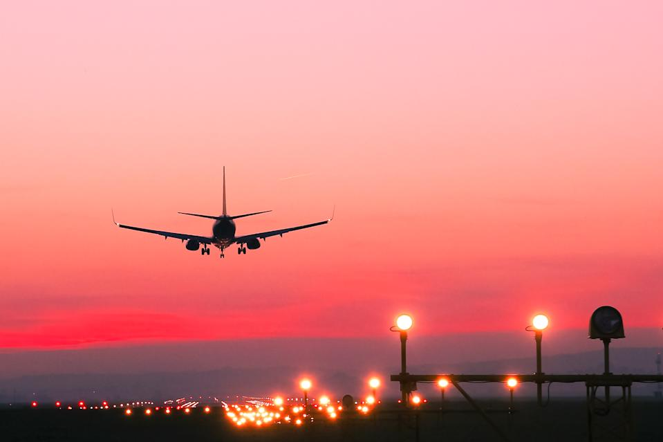 Plane lands at an airfield at the sunset