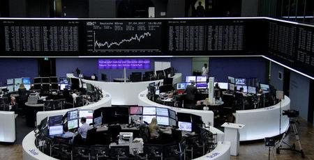 FILE PHOTO: Traders work at their desks in front of the German share price index, DAX board, at the stock exchange in Frankfurt, Germany, April 27, 2017. REUTERS/Staff/Remote