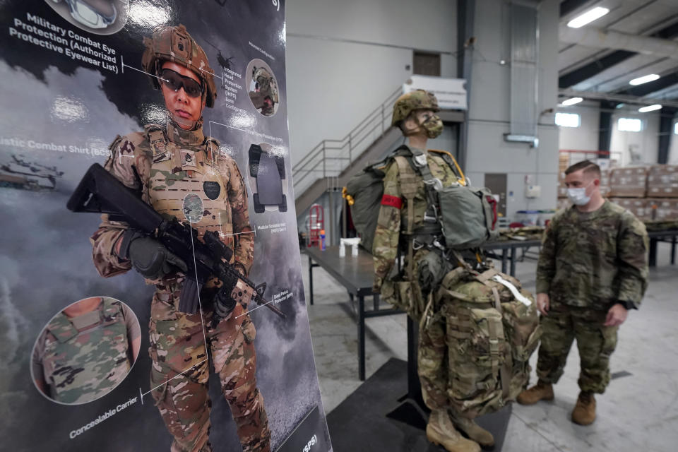 """An illustration and mannequin are displayed for members of the 82nd Airborne Division as the new generation of """"modular scalable vest: are being issued at Fort Bragg, N.C., Wednesday, Sept. 22, 2021. The Army for the first time, began handing out armor that now comes in three additional sizes, and can be adjusted in multiple ways to fit better and allow soldiers to move faster and more freely. The so-called """"modular, scalable vest"""" was is being distributed to soldiers at Fort Bragg, N.C., along with new versions of the combat shirt that are tailored to better fit women, with shorter sleeves and a flare at the bottom where it hits their hips. (AP Photo/Gerry Broome)"""