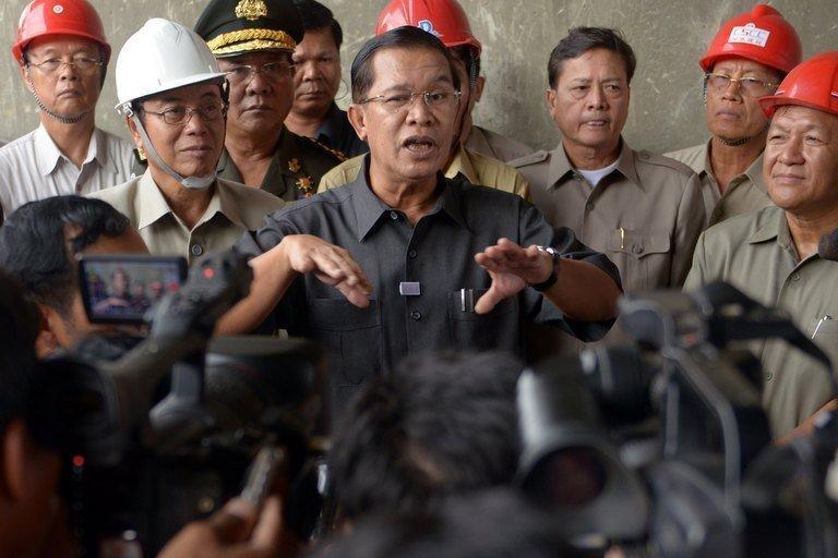 Cambodian Prime Minister Hun Sen (C) speaks to the media during his visit to a construction site in Phnom Penh on July 31, 2013. Hun Sen last Sunday claimed it had secured an estimated 68 of the 123 lower house seats, defeating the CNRP which won 55