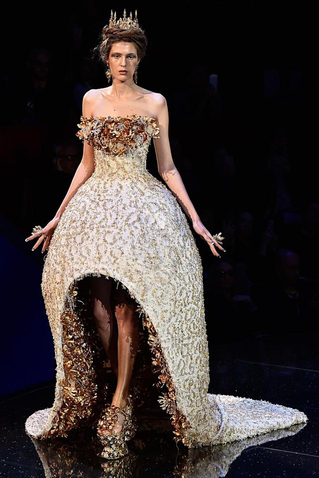 <p>Model wears a voluminous, strapless gown featuring opulent gold floral embellishments from the Guo Pei SS18 Haute Couture show. (Photo: Getty Images) </p>
