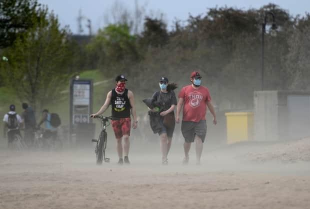 The wind blows sand into the air as three masked beachgoers take in the warm weather at Mooney's Bay beach in Ottawa May 15, 2021.