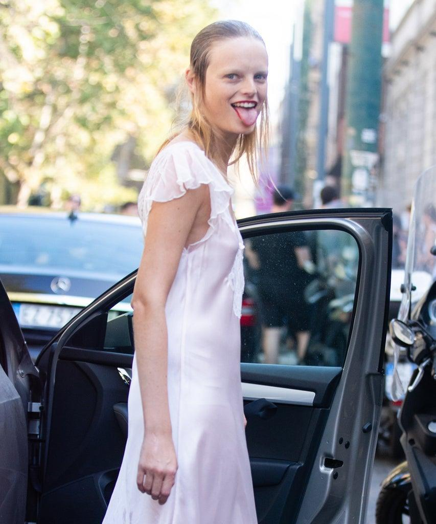 MILAN, ITALY – SEPTEMBER 23: Model Hanne Gaby Odiele sticks her tongue out in a light pink white slip dress after the Marni show during Milan Fashion Week Spring/Summer 2019 on September 23, 2018 in Milan, Italy.