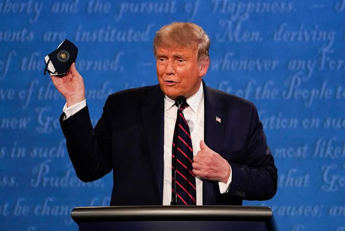 Trump holds up his face mask during the first presidential debate on Tuesday. (Photo: ASSOCIATED PRESS)