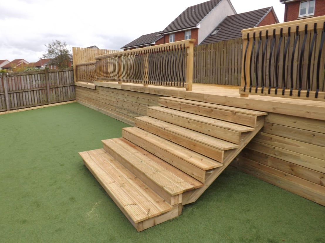 """<p>Bet you didn't expect this... at the other end of this backyard spot one gorgeous timber deck, complete with wooden steps and iron railings, add another big batch of style and potential!</p><p>Architects, gardeners, and many more – we have them all here on homify. See our<a rel=""""nofollow"""" href=""""https://www.homify.co.uk/professionals"""">professionals</a> page for more info.</p>  Credits: homify / Decking Design limited"""