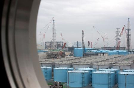 FILE PHOTO: Storage tanks for contaminated water are seen through a window of a building at TEPCO's Fukushima Daiichi nuclear power plant in Okuma