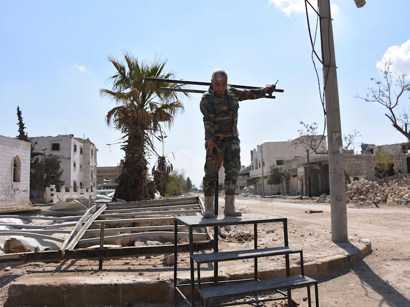 A Syrian soldier demonstrates how the crucifixion stand erected and used by Isis works: photography by George Ourfalian