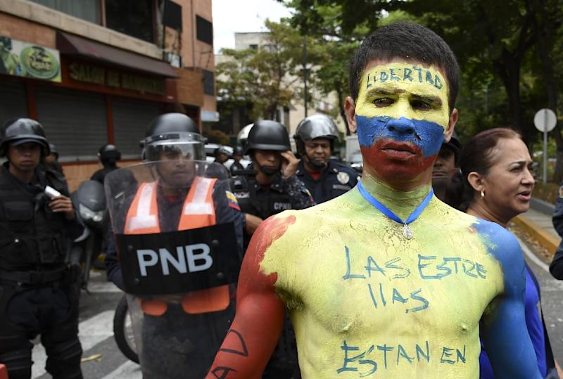 A man with his body painted in the Venezuelan national flag's colors demonstrates in front of riot police near La Carlota Air Base in Caracas on May 4, 2019 (AFP Photo/YURI CORTEZ)