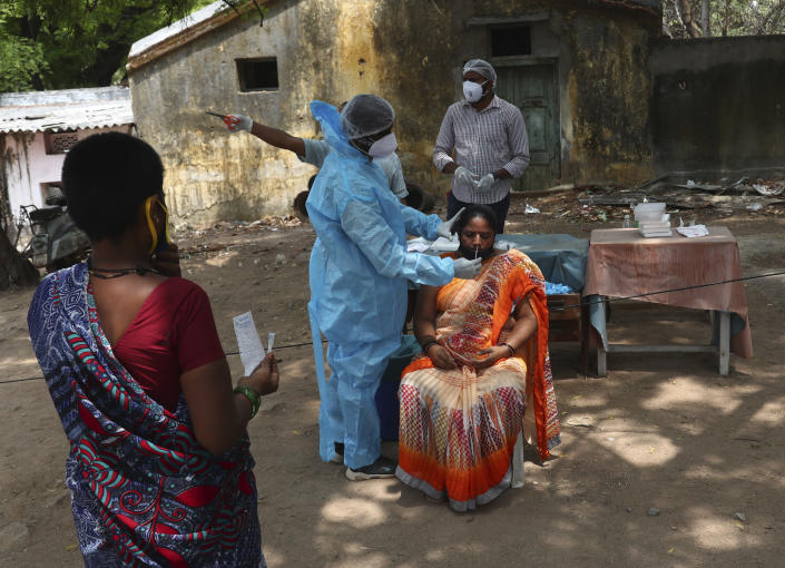 A health worker takes a nasal swab sample of a woman to test for COVID-19 in Hyderabad, India, Friday, May 7, 2021. With coronavirus cases surging to record levels, Indian Prime Minister Narendra Modi is facing growing pressure to impose a harsh nationwide lockdown amid a debate whether restrictions imposed by individual states are enough. (AP Photo /Mahesh Kumar A.)