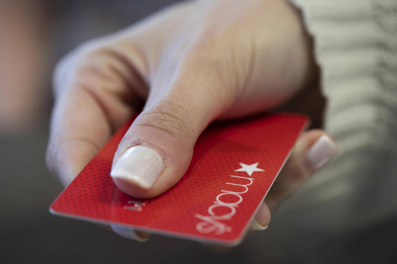 In this Sunday, Aug. 11, 2019, photo a woman holds a Macy's card in New Orleans. Macy's is lowering its annual earnings guidance after the department store struggled with a big earnings miss during the second quarter as it was forced to slash prices on unsold merchandise. The department store said Wednesday, Aug. 14, that a combination of factors including a fashion miss, slow sell-through of warm weather clothing on top of a worsening climate for tourism led to rising inventory levels. (AP Photo/Jenny Kane)