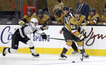 Vegas Golden Knights Dylan Coghlan (52) looks to pass as Los Angeles Kings center Lias Andersson (24) defends during the first period of an NHL hockey game Sunday, Feb. 7, 2021, in Las Vegas. (AP Photo/Isaac Brekken)