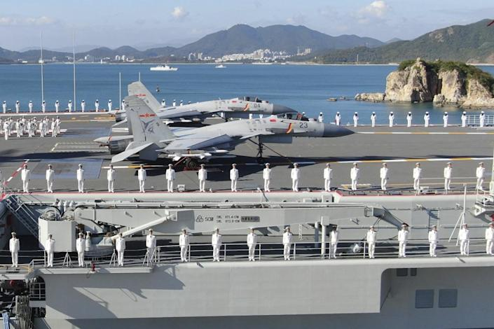 China's new Shandong aircraft carrier lined with sailors