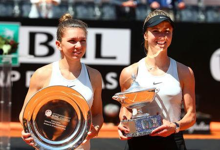 Tennis - WTA Premier 5 - Italian Open - Foro Italico, Rome, Italy - May 20, 2018 Ukraine's Elina Svitolina celebrates with the trophy after winning the Italian Open as Romania's Simona Halep looks on with her runner up trophy REUTERS/Tony Gentile