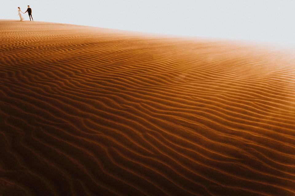 <p>A newlywed couple is seen on the furrowed sand dunes of Maspalomas Dunes in the Canary Islands. (Photo: Junebug Weddings/Caters News) </p>