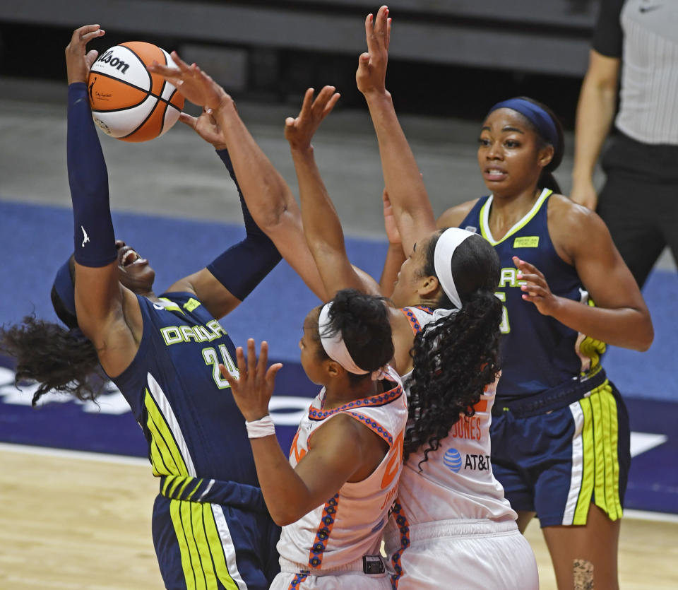 Connecticut Sun guard Briann January, center, commits the foul on Dallas Wings guard Airka Ogunbowale during a WNBA basketball game Tuesday, June 22, 2021 at Mohegan Sun Arena in Uncasville, Conn. (Sean D. Elliot/The Day via AP)