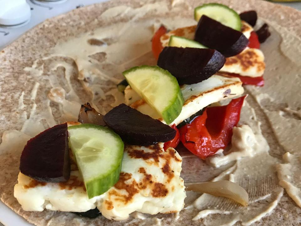 A wholemeal wrap spread with hummus and topped with roasted peppers, halloumi, cucumber, and beetroot.