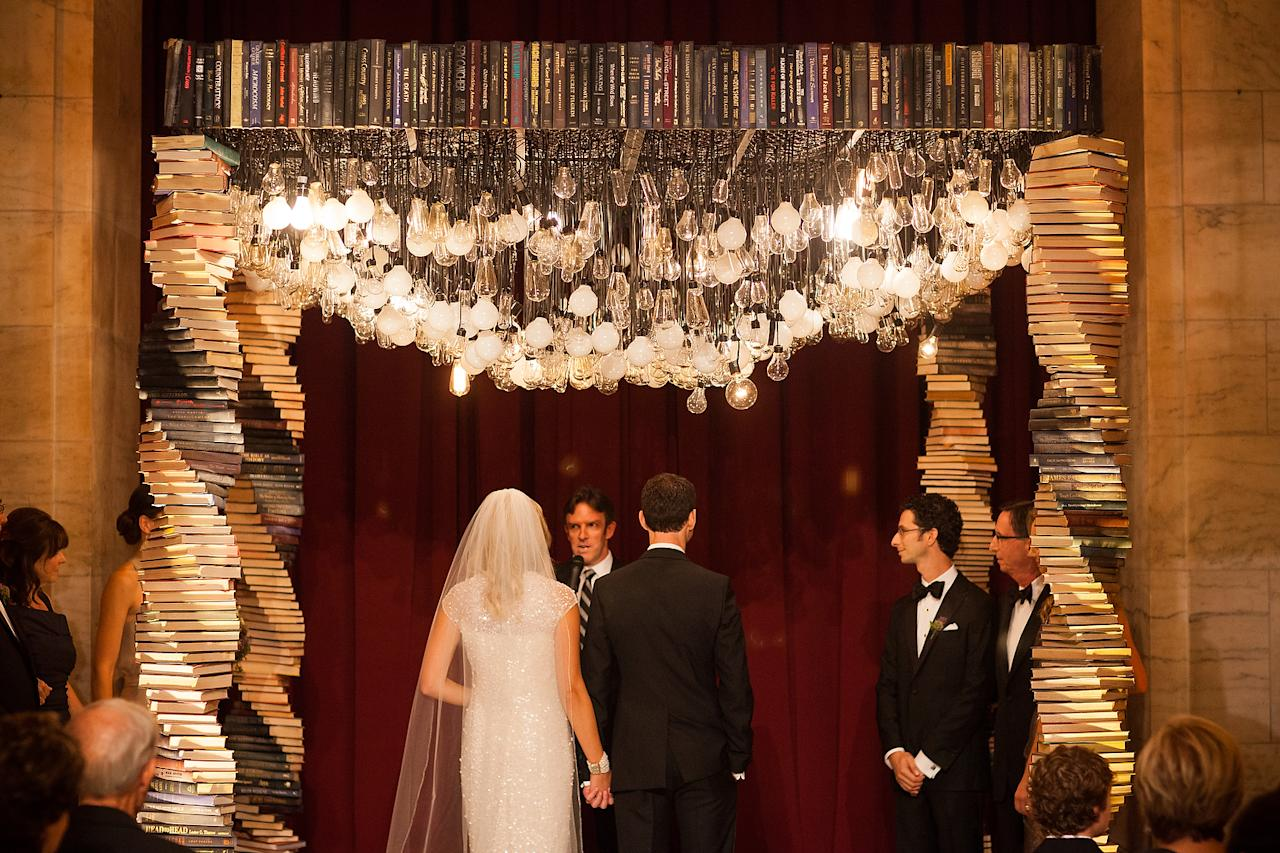 """<p>This may just be every <a rel=""""nofollow"""" href=""""http://www.elledecor.com/design-decorate/room-ideas/g2933/home-libraries/"""">book lover</a>'s dream come true. The New York Public Library hosted this literary wedding, which featured a chuppah made of antique books and topped with hundreds of lightbulbs. Librarians helped guests find their seats and guests were even given library card catalogue escort cards. </p><p><em>Via <a rel=""""nofollow"""" href=""""http://www.smashingtheglass.com/book-themed-wedding-at-the-new-york-public-library-new-york-usa/"""">Smashing The Glass</a></em><br></p>"""