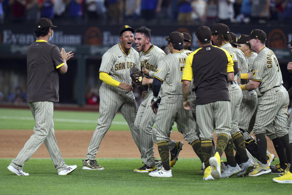 San Diego Padres starting pitcher Joe Musgrove (44) is mobbed by teammates after pitching a no-hitter against the Texas Rangers in a baseball game Friday, April 9, 2021, in Arlington, Texas. (AP Photo/Richard W. Rodriguez)