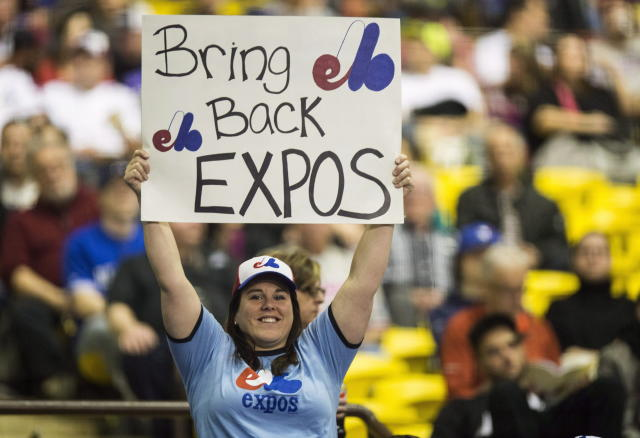 FILE - In this April 3, 2015, file photo, a fan holds up a sign during a pregame ceremony as the Toronto Blue Jays face the Cincinnati Reds in an exhibition baseball game in Montreal. The Tampa Bay Rays have received permission from Major League Baseball's executive council to explore a plan that could see the team split its home games between the Tampa Bay area and Montreal. (Paul Chiasson/The Canadian Press via AP, File)