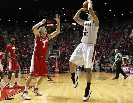 San Diego State guard James Rahon, front right, scores over New Mexico Lobos' Hugh Greenwood during the first half of anNCAA basketball game on Wednesday, Feb. 15, 2012, in San Diego. (AP Photo/Lenny Ignelzi )