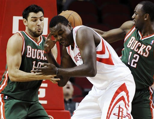 Houston Rockets' Samuel Dalembert, center, loses the ball to Milwaukee Bucks' Carlos Delfino (10) and Luc Mbah a Moute (12) in the first half of an NBA basketball game, Wednesday, Jan. 25, 2012, in Houston. (AP Photo/Pat Sullivan)